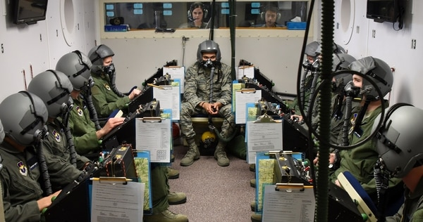 Senior Airman Kristyn Widger, 82nd Aerospace Medical Squadron physiology technician, gives instructions to Pilot Training Next students during a hypobaric chamber flight at Sheppard Air Force Base, Texas, March 1. (Senior Airman Robert McIlrath/Air Force)