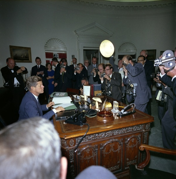 Photographers and film cameramen swarmed President John F. Kennedy at his desk in the Oval Office upon signing the Cuba Quarantine order, 23 October 1962. (Robert Knudsen/ John F. Kennedy Presidential Library and Museum, Boston)
