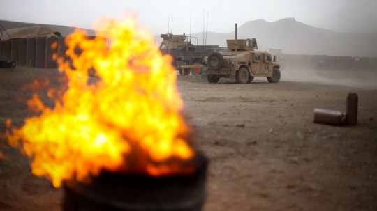 Wind fans the flames of a burn pit at Combat Outpost Tangi in the Tangi Valley of Afghanistan on Aug. 31, 2009. (Staff Sgt. Teddy Wade/Army)