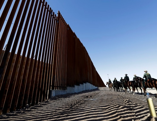 In this Oct. 26, 2018, file photo, mounted Border Patrol agents ride along a newly fortified border wall structure in Calexico, Calif. President Donald Trump is visiting Calexico on Friday, April 5, 2019, to tour the recently built portion of the border fence that bears a silver plaque with his name on it. (Gregory Bull/AP)