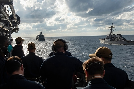 The cruiser Vella Gulf and the destroyer Laboon, right, come alongside the fleet-replenishment oiler USNS Kanawha in the Atlantic Ocean Jan. 15. Crew members of both ships have benefited from a new Navy program to provide emotional support to deploying sailors. (MC2 Dean Cates/Navy)