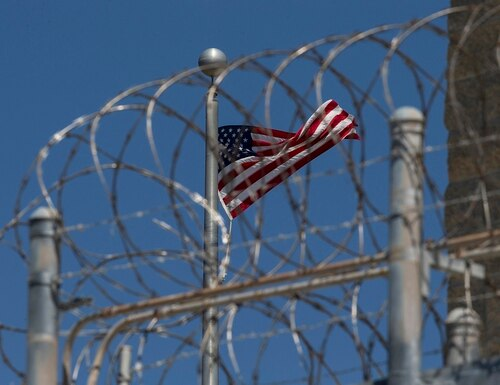 In this April 17, 2019, file photo reviewed by U.S. military officials, a U.S. flag flies inside the razor wire of the Camp VI detention facility at Guantanamo Bay Naval Base, Cuba. (Alex Brandon/AP)