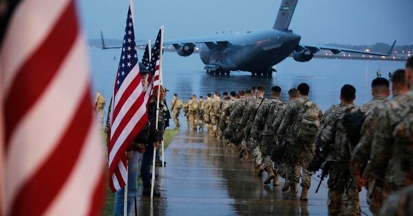 Paratroopers assigned to 1st Brigade Combat Team, 82nd Airborne Division walk as they prepare equipment and load aircraft bound for the U.S. Central Command area of operations from Fort Bragg, N.C., Saturday, Jan. 4, 2020. (Spc. Hubert Delany III/U.S. Army via AP)