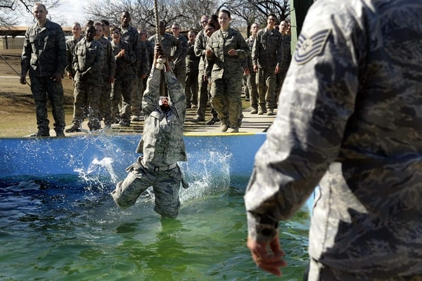 A basic trainee swings across a cold water pool at the obstacle course. The newly expanded Air Force Basic Military Training program focuses on a