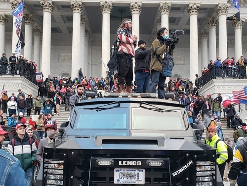 Pro-Trump groups occupy the steps of the Capitol building and stand atop an armored government vehicle Jan. 6, 2021. (Kyle Rempfer/Staff)