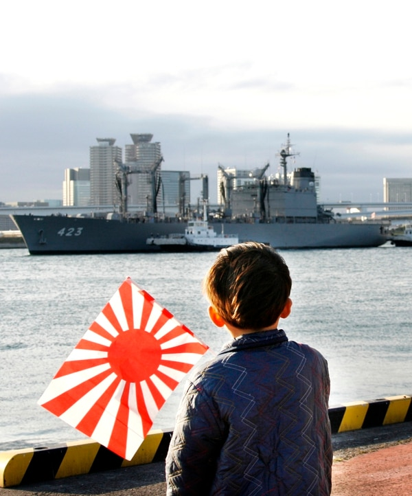 In this Nov. 23, 2007, photo, a Japanese boy waves the navy sun flag as Japan's Maritime Self-Defense Force supply vessel Tokiwa returns to Tokyo's Harumi Pier from the Indian Ocean ending a six-year mission in support of Afghan coalition troops. (Shizuo Kambayashi/AP)