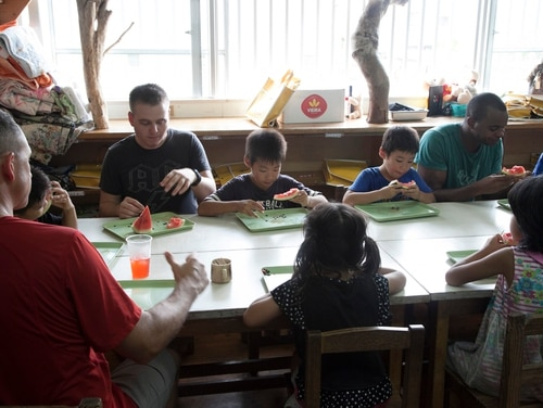 Marines from III Marine Expeditionary Force share a snack with students at the Himawari Gakudo Day Care Center in Nago City, Japan, on Aug. 23, 2014. (Lance Cpl. David N. Hersey/Marine Corps)