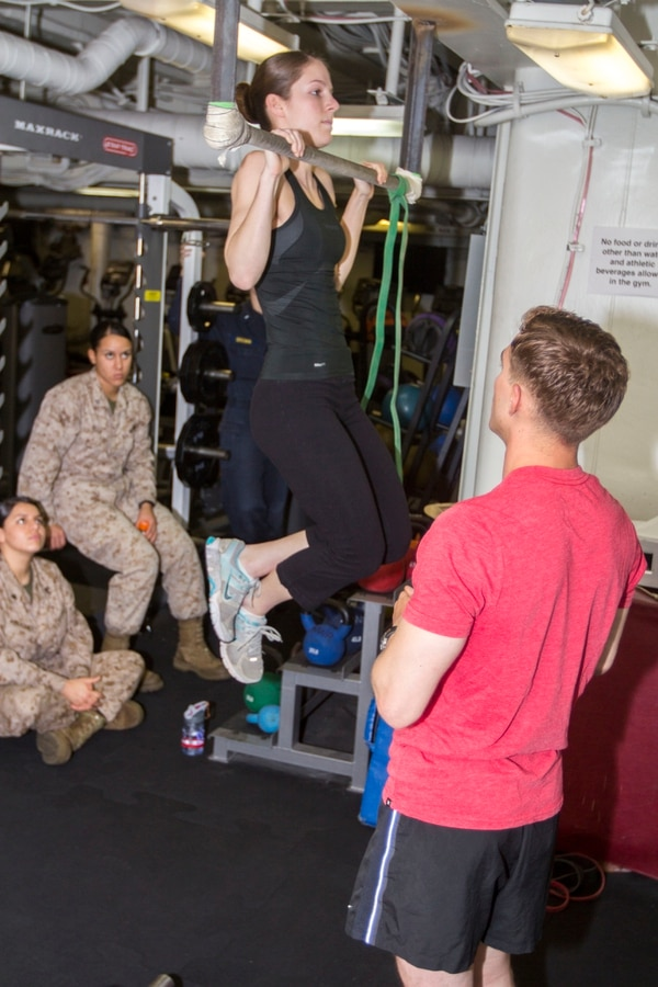 U.S. Marine Sgt. James Vincent, explosive ordnance disposal technician assigned to the 26th Marine Expeditionary Unit (MEU), explains the various muscle groups used while performing pull ups as Lance Cpl. Ashley Vallera, a signals intelligence analyst assigned to the 26th MEU, demonstrates the exercise during a period of professional military education in the gym of the USS Kearsarge, at sea, June 7, 2013. The 26th MEU is a Marine Air-Ground Task Force forward-deployed to the U.S. 5th Fleet area of responsibility aboard the Kearsarge Amphibious Ready Group serving as a sea-based, expeditionary crisis response force capable of conducting amphibious operations across the full range of military operations. (U.S. Marine Corps photo by Cpl. Kyle N. Runnels/Released)