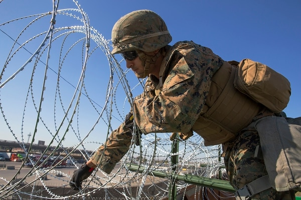 A U.S. Marine with 7th Engineer Support Battalion, Special Purpose Marine Air-Ground Task Force 7, lays barbed wire onto the California-Mexico border at the Otay Mesa Port of Entry in California, Nov. 18, 2018. (Sgt. Asia J. Sorenson/Marine Corps)