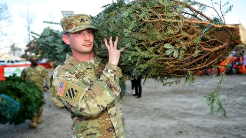 Staff Sgt. Nicholas Guilbault hauls away his Christmas tree during the annual Trees For Troops