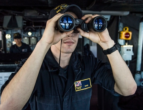 A junior officer looks through binoculars while standing watch on the bridge aboard the destroyer Carney. (MC2 James Turner/Navy)