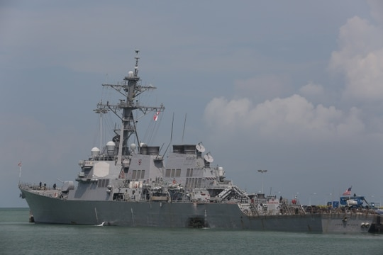 The destroyer John S. McCain moored pier side at Changi Naval Base, Singapore, following an Aug. 21, 2017, collision with an oil tanker that killed 10 sailors. (Grady T. Fontana/Navy)