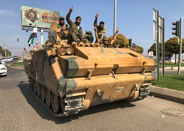 Turkish-backed Syrian opposition fighters ride atop their armored personnel carrier to cross the border into Syria, in Akcakale, Sanliurfa province, southeastern Turkey in this Oct. 18, 2019. (Mehmet Guzel/AP