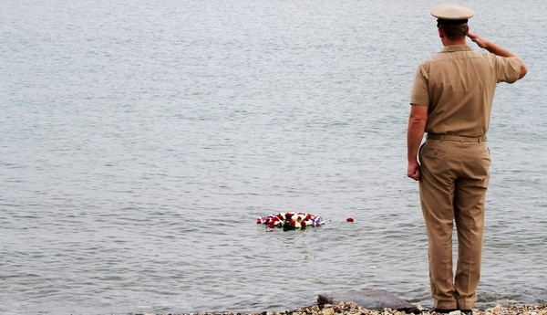 Navy Capt. John R. Nettleton holds his salute after he tossed a commemorative wreath into the bay during Naval Station Guantanamo Bay's 2014 ceremony remembering the Battle of Midway. He's since been indicted for lying to authorities about a scandal there. (Department of Defense)