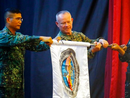 Co-exercise directors Lt. Gen. Lawrence Nicholson, center, commander of the 3rd U.S. Marine Expeditionary Forces, and Northern Luzon commander Lt. Gen. Emmanuel Salamat, left, unfurl a flag of the joint U.S.-Philippines military exercise dubbed