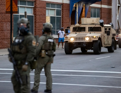 National Guard vehicles drive into downtown behind police officers in riot gear as protests occur on May 30, 2020, in Louisville, Ky. (Brett Carlsen/Getty Images)
