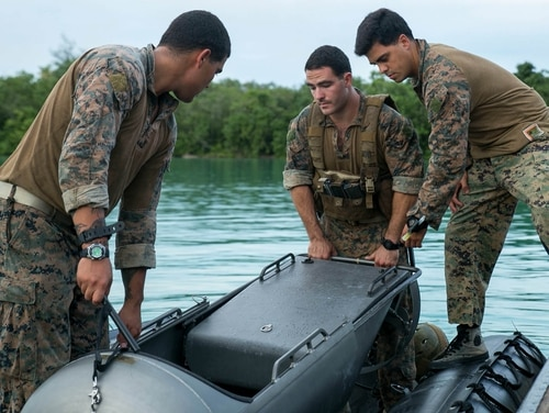Marines load a diver propulsion device into a combat rubber raiding craft Sept. 20 at U.S. Naval Base Guam during Exercise Valiant Shield 2014. The DPDs will aid the Marines conduct night infiltration, in which Marines will quietly come ashore once night falls. Valiant Shield is a U.S.-only exercise integrating Navy, Air Force, Army, and Marine Corps assets, offering real-world joint operational experience to develop capabilities that provide a full range of options to defend U.S. interests and those of its allies and partners. The Marines are reconnaissance men with 3rd Reconnaissance Battalion, 3rd Marine Division, III Marine Expeditionary Force. (U.S. Marine Corps photo by Cpl. Lena Wakayama/Released)