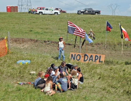 Bill Left Hand, of McLaughlin, South Dakota, stands next to a sign at the site of a protest against construction of the Dakota Access Pipeline, Thursday, Aug. 11, 2016, in Morton County, N.D. Authorities have arrested at least five people in southern North Dakota protesting the $3.8 billion Dakota Access Pipeline from North Dakota to Illinois. (Tom Stromme/The Bismarck Tribune via AP)