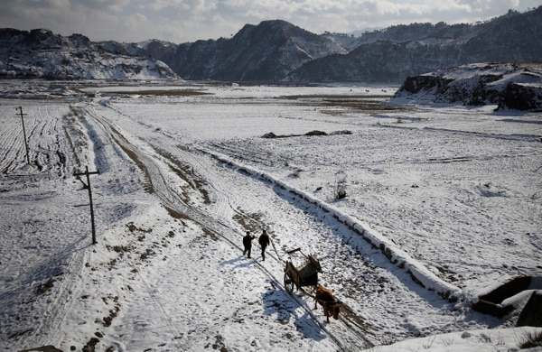In this Thursday, Dec. 3, 2015, photo, farmers transport their supplies in an oxcart while the Chongchon River No. 10 Hydroelectric Power Station is seen in the background in Ryongyon-ri in Kujang county, North Korea.
