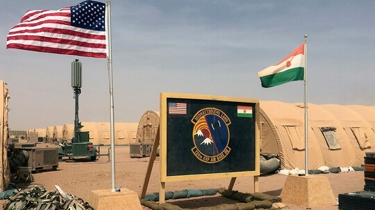 In this photo taken April 16, U.S. and Nigerien flags are raised side by side at the base camp for air forces and other personnel supporting the construction of Niger Air Base 201 in Agadez. (Carley Petesch/AP)