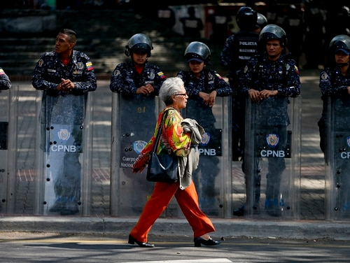 Police stand guard in anticipation of a march called by a coalition of opposition parties and civic groups who are petitioning lawmakers for a law of guarantees that will protect workers who have been victims of political retaliation and unjustified dismissals, in Caracas, Venezuela, Tuesday, March 19, 2019. (Natacha Pisarenko/AP)