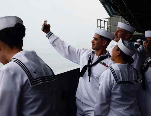 Sailors take a group photo before manning the rails as the aircraft carrier Theodore Roosevelt arrives at Naval Air Station North Island May 25, following a deployment to U.S. 7th Fleet. (MCSN Joseph Pircbrown/Navy)