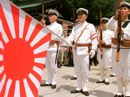 In this Aug. 15, 1999, photo, Japanese war veterans in Japan's Imperial Navy uniform stand at attention with the navy flag as they pay their respects to the war dead at Tokyo's Yasukuni Shrine, commemorating the end of World War II. Japan has announced it is not inviting South Korea to an upcoming multinational naval review it is hosting next month because their ties are badly strained over history, trade and defense. (/Tsugufumi Matsumoto/AP)