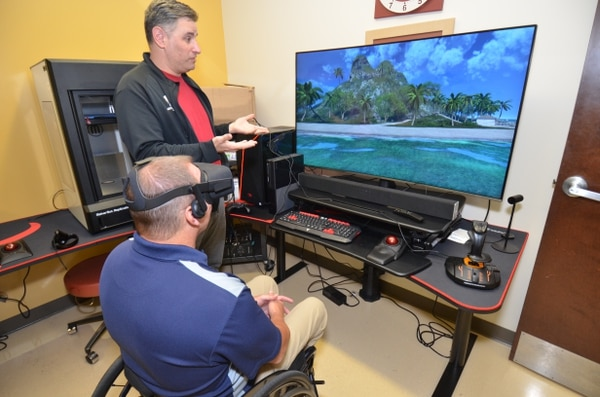 Recreation Therapist Jamie Kaplan shows Army veteran Geoff Hopkins how to use a virtual reality program at James A. Haley Veterans' Hospital in Tampa, Fla. Hopkins has been in a wheelchair since 1988, when he was injured in a motorcycle accident. (Ed Drohan/James A. Haley Veterans' Hospital)