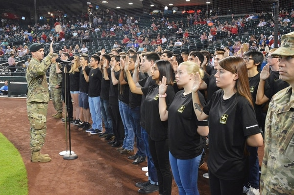 Lt. Col. Scott Morley administers the oath of enlistment to 40 future soldiers from Phoenix. The Army is offering additional pay for recruiters to extend their tours. (Mike Scheck/Army)