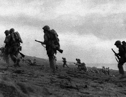 Original caption from 1945: Without a scrap of cover in sight, U.S. Marines plod through volcanic sand as they start their advance inland in the bloodiest of their battles, on Iwo Jima, March 2, 1945. Their third airfield on Iwo and the end of the battle is not far off. (Paige Abbott/INP/AP)