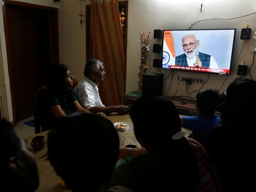 An Indian family watches Indian Prime Minister Narendra Modi addressing the nation on a television in Prayagraj, Uttar Pradesh state, India, on March 27, 2019. (Rajesh Kumar Singh/AP)