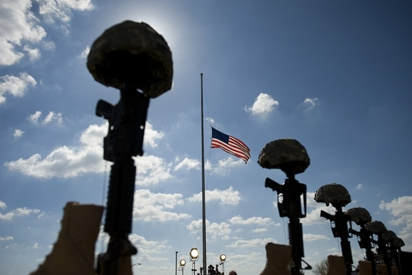 A fallen soldiers memorial is silhouetted in front of the podium where the memorial service that US President Barack Obama and first lady Michelle Obama will attend for the thirteen victims of the shooting rampage by US Army Major Nidal Malik Hasan on November 10, 2009 in Fort Hood, Texas. Hasan, an army psychiatrist, killed 13 people and wounded 30 in a shooting at the military base on November 5, 2009. AFP PHOTO/Jim WATSON