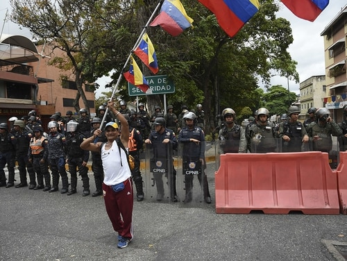 A man flutters Venezuelan national flags in front of a line of police during an opposition demonstration calling for the armed forces to disobey Venezuelan President Nicolas Maduro near La Carlota Air Base in Caracas on May 4, 2019. (Yuri Cortez/AFP via Getty Images)