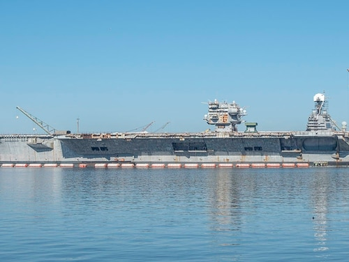 The hulk of the ex-aircraft carrier Enterprise is tied up across from the pier from the Navy's newest aircraft carrier, the Gerald R Ford, at the Huntington Ingalls Newport News Shipyard, Feb. 5. (Mark D. Faram/Staff)