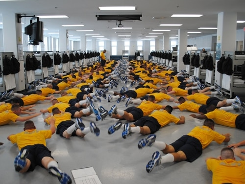 140725-N-BM955-044 GREAT LAKES, Ill. (July 25, 2014) Seaman recruits perform physical training exercises in their berthing compartment at Recruit Training Command (RTC). Recruit divisions conduct various physical training exercises in order to build strength in preparation for their final training assessments and duty in the fleet. RTC is known as the Quarterdeck of the Navy and trains approximately 37,000 civilians into basically trained Sailors. (U.S. Navy photo by Mass Communication Specialist 1st Class Richard Perez/Released)