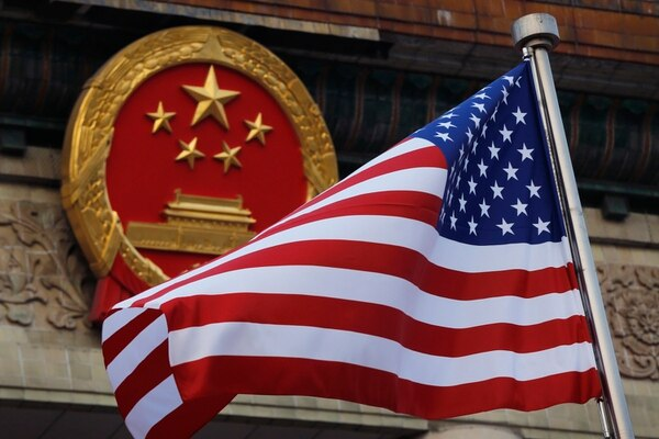 An American flag is flown next to the Chinese national emblem during a welcome ceremony for visiting U.S. President Donald Trump outside the Great Hall of the People in Beijing, Thursday, Nov. 9, 2017. (Andy Wong/AP)