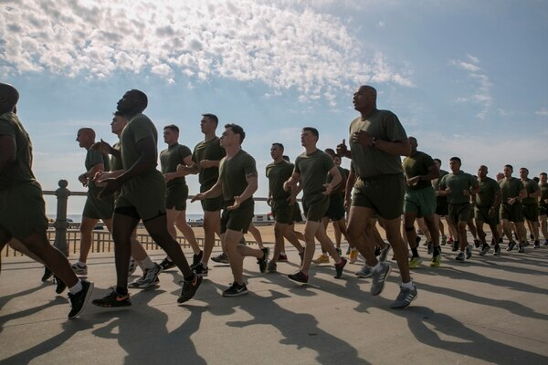 Sgt. Maj. Adam Moore, battalion sergeant major, H&S Battalion, U.S. Marine Corps Forces Command calls cadence as Marines from MARFORCOM in a formation run on the boardwalk, Virginia Beach, Va., June 30. The run was a chance to get away from the typical battalion physical training, and build esprit de corps and camaraderie among the Marines in a different setting. (Photo by Cpl. Logan Snyder/Marine Corps)
