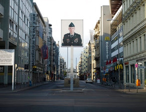 FILE - In this June 9, 2020, file photo, a picture of a former American soldier is displayed at the former U.S. army Checkpoint Charlie in Berlin, Germany. (AP Photo/Markus Schreiber, File)