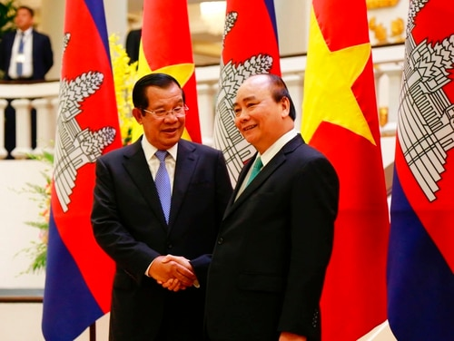 Cambodian Prime Minister Hun Sen, left, shakes hands with his Vietnamese counterpart Nguyen Xuan Phuc before heading for talks behind closed doors in Hanoi on Dec. 7. (Tran Van Minh/AP)