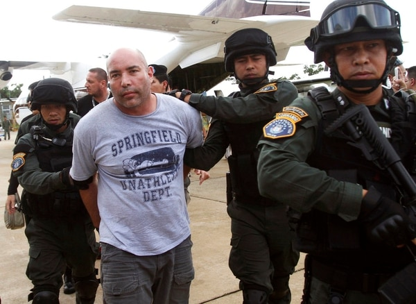 In this Sept. 26, 2013, file photo, Joseph Hunter, second from left, a former U.S. Army sniper who became a private mercenary, is in the custody of Thai police commandos after being arrested in Bangkok, Thailand. Hunter, already serving a 20 year term for plotting to kill a DEA agent, goes on trial in New York at the U.S. District Court in Manhattan on April 3, 2018, on charges that he plotted to assassinate a real-estate agent for an international crime boss. (Sakchai Lalit/AP)