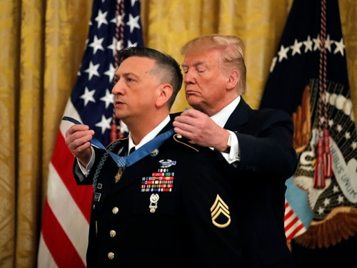 President Donald Trump awards Army Staff Sgt. David Bellavia the Medal of Honor at the White House in Washington, Tuesday, June 25, 2019. Bellavia is a Iraq veteran who cleared an insurgent strongpoint and allowed members of his platoon to move to safety. (AP Photo/Carolyn Kaster)