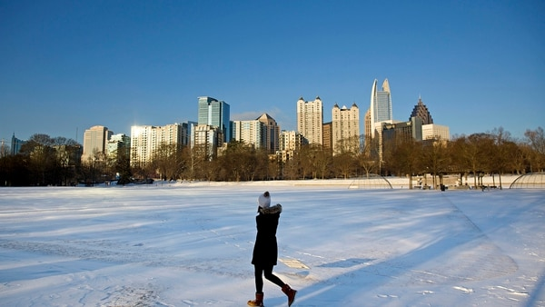 A person walks through a snow covered Piedmont Park as the midtown skyline stands in the background Wednesday, Jan. 17, 2018. Georgia state officials are working to convince the Army to locate the Army Futures Command in the city. (David Goldman/AP)