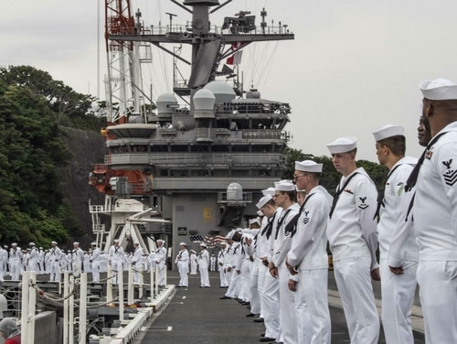 Sailors man the rails of the aircraft carrier Ronald Reagan as the ship leaves its Japan port this week for an annual spring patrol. The deployment was delayed to a