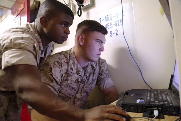 Gunnery Sgt. Lagarian Smith, cyber network chief with the 13th Marine Expeditionary Unit, guides Cpl. Justin Henderson, a 13th MEU cyber network specialist, through troubleshooting techniques as they set up network communications aboard the USS Boxer during PHIBRON-MEU Intergration (PMINT) exercise Sept. 24, 2015. The exercise marks the first time 13th MEU Marines and Sailors with the Boxer Amphibious Ready Group get to work together at sea before their deployment to the Pacific and Central Command areas of responsibility in early 2016. (U.S. Marine Corps photo by: Staff Sgt. Terika S. King/Relased)