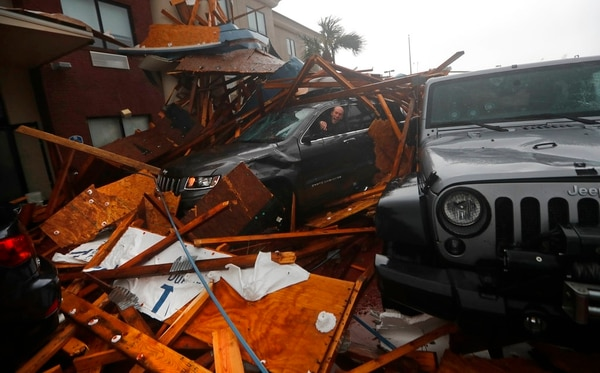 A storm chaser climbs into his vehicle during the eye of Hurricane Michael to retrieve equipment after a hotel canopy collapsed in Panama City Beach, Fla., on Wednesday. (Gerald Herbert/AP)