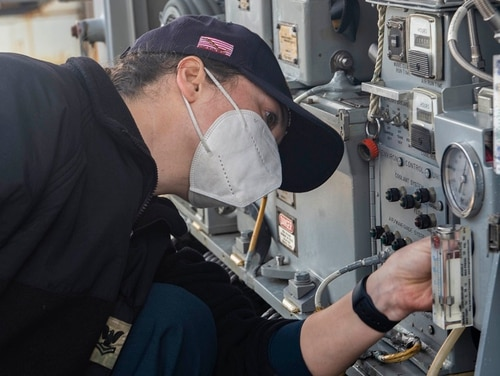Fire Controlman 2nd Class Katherine Verbeek inspects a close-in weapons system aboard the guided-missile cruiser Vella Gulf Feb. 16 during pier-side routine maintenance. The warship has suffered a fuel leak that is forcing it to return to Norfolk, less than a week into its deployment. (MC2 Dean Cates/Navy)