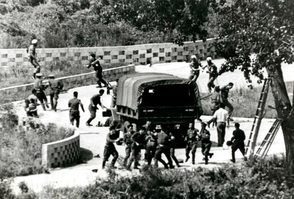 In this Aug. 18, 1976, file photo, North Korean soldiers attack United Nations Command personnel wearing helmets at the truce village of Panmunjom, South Korea. Two American soldiers were hacked to death by ax-wielding North Korean soldiers during a fight over U.S. efforts to trim a poplar tree at the Korean Demilitarized Zone that bisects the two Koreas. (Yonhap via AP)