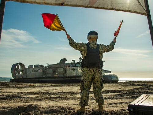 Information Systems Technician 2nd Class Tyler Frierson, Beach Master Unit 1, Naval Beach Group 1, guides a Landing Craft Air Cushion during Pacific Blitz 19 at Marine Corps Base Camp Pendleton on March 22. (Lance Cpl. Betzabeth Y. Galvan/Navy)
