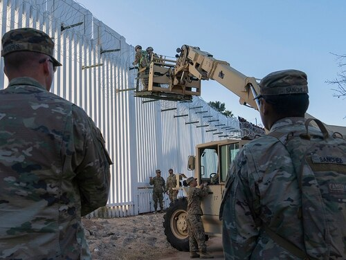 Military policemen stand watch as soldiers with the 515th Sapper Company, 5th Engineer Battalion, 36th Engineer Brigade make repairs on concertina wire Dec. 19, 2018, at Nogales, Ariz. (Sgt. Brandon Banzhaf/Army)