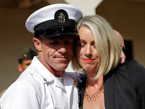 "Special Warfare Operator Chief Edward ""Eddie"" Gallagher, left, and his wife Andrea hug after leaving the Naval Base San Diego courthouse on July 2 after he had been acquitted on all but one charge at his court-martial trial. (Gregory Bull/AP)"